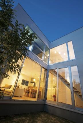 夕暮れになると大開口の窓から室内の明かりが中庭へと舞い込み、中庭に配<br /> された間接照明と光のコラボを果たし、煌びやかな非日常空間を創り出す。