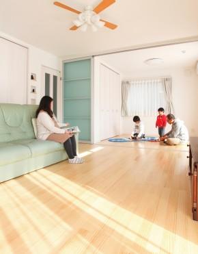 温かな陽射しが家族団欒の空間にたっぷり差し込むよう、巧みにプランニングされている。リビングとつながる洋室はパーテーションで仕切って使うこともできる。床にはうづくり仕上げの無垢フローリングを使用。個性的な表情を描くうづくり加工が美しい立体感を生んでいる。